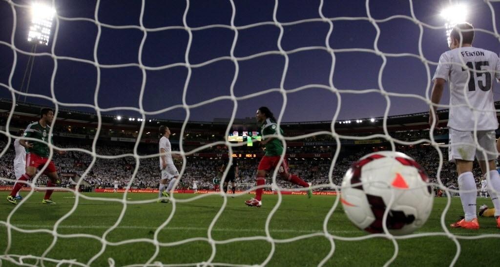 20.nov.2013 - A bola é vista no fundo do gol após Carlos Peña anotar o quarto mexicano na vitória por 4 a 2 sobre a Nova Zelândia no jogo de volta da repescagem mundial; resultado classificou o México para a Copa-2014