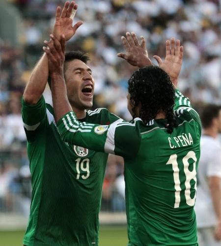 20.nov.2013 - Peralta comemora com Peña um de seus três gols na partida que deu ao México a vaga na Copa: 4 a 2 na Nova Zelândia