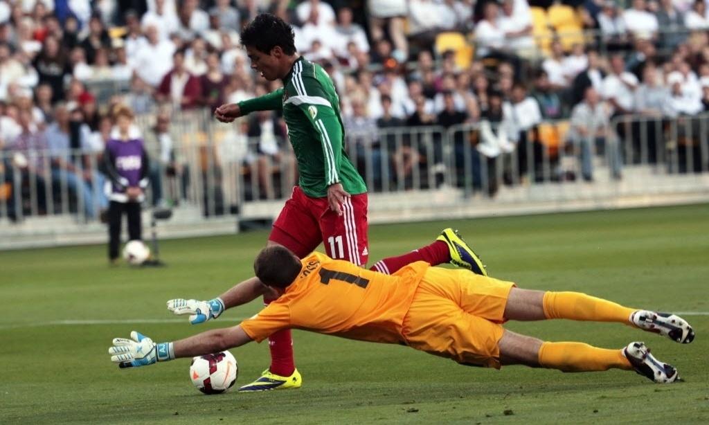 20.nov.2013 - Raul Jimenez tenta driblar o goleiro Glen Moss durante o duelo entre México e Nova Zelândia na repescagem mundial da Copa-2014; mexicanos venceram por 4 a 2 e se classificaram para o Mundial