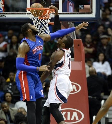 20.nov.2013 - Paul Millsap, do Atlanta Hawks, consegue enterrar mesmo atingido no rosto pelo braço de Andre Drummond, do Detroit Pistons; os Hawks venceram por 93 a 85