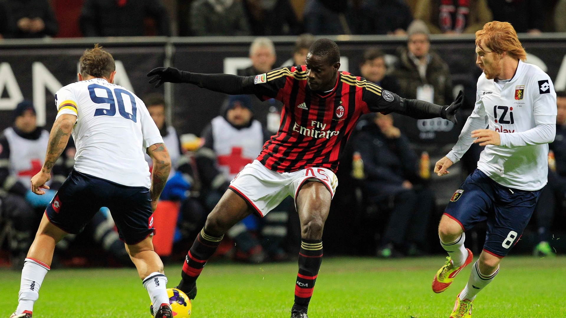 23.nov.2013 - Mario Balotelli tenta escapar da marcação de dois jogadores do Genoa