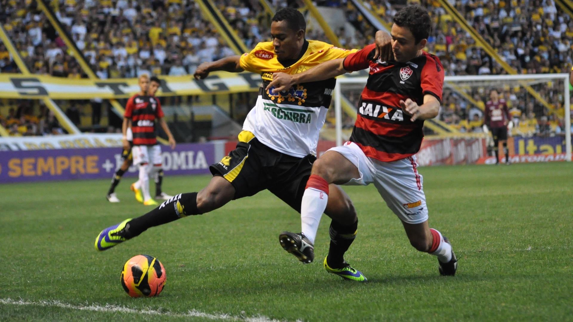 Lins, atacante do Criciúma, e Juan, lateral do Vitória, disputam a bola próxima à linha lateral (23.nov.13)