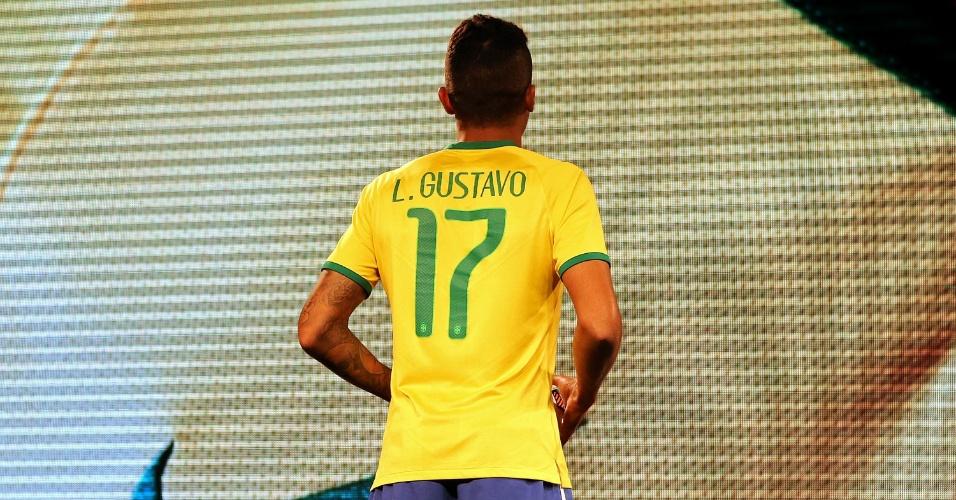 Volante Luiz Gustavo exibe a camisa a ser usada pela seleção brasileira na Copa do Mundo de 2014 (24.nov.2013)