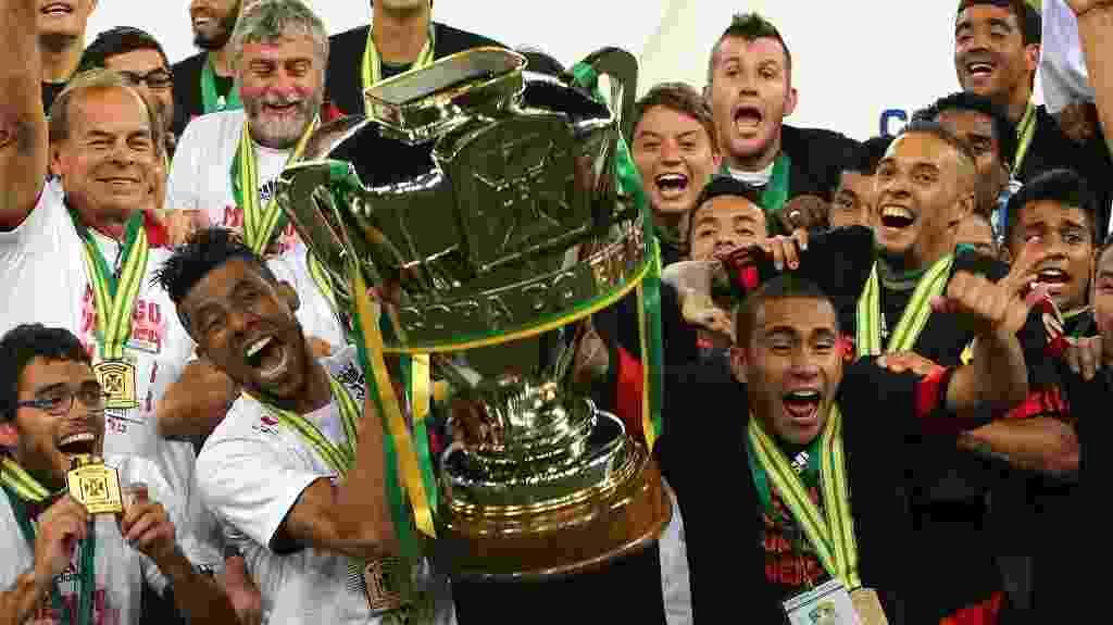 27.nov.2013 - Léo Moura ergue a taça de campeão da Copa do Brasil de 2013 após vitória do Flamengo sobre o Atlético-PR - Julio Cesar Guimaraes/UOL