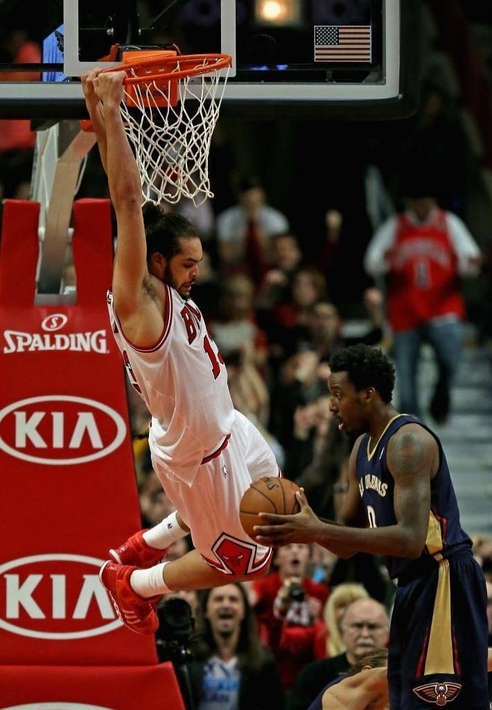 02.dez.2013 - O francês Joakim Noah enterra e se pendura no aro durante a derrota do Chicago Bulls para o New Orleans Pelicans, após 3 prorrogações, por 131 a 128