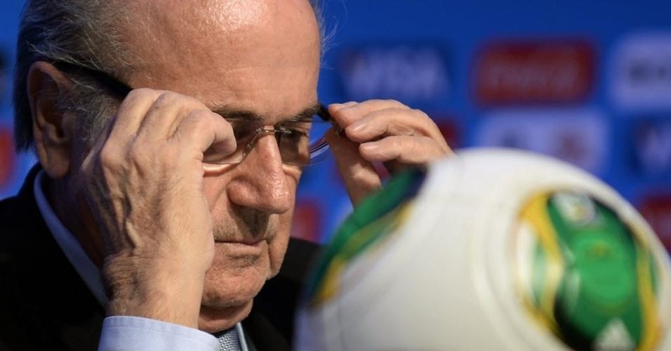 03.dez.2013 - Joseph Blatter (dir.), presidente da Fifa, arruma os óculos durante conversa com a imprensa na Cosa do Sauípe, na Bahia, local onde acontecerá os sorteios dos grupos para a Copa do Mundo