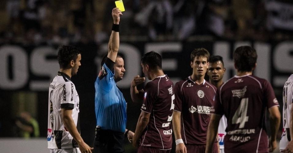 04.dez.2013 - Árbitro Roberto Silvera aplica o cartão amarelo em Diego González durante partida entre Ponte Preta e Lanús