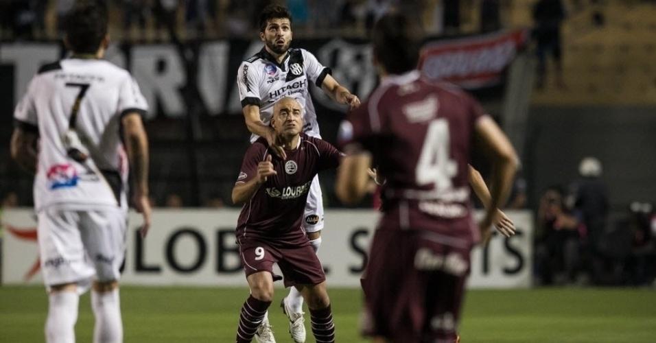 04.dez.2013 - Diego Sacoman disputa a bola com Santiago Silva durante partida entre Ponte Preta e Lanús