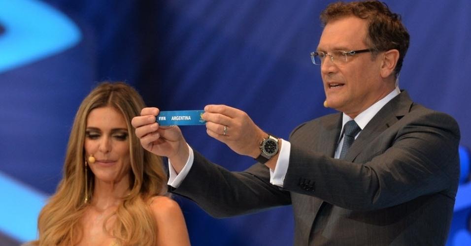 06.dez.2013 - Fernanda Lima (esq.) observa enquanto Jérôme Valcke mostra o nome da Argentina durante sorteio dos grupos da Copa do Mundo
