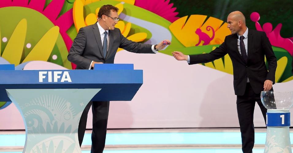 Zidane entrega a 'bolinha' para Valcke durante sorteio dos grupos da Copa do Mundo