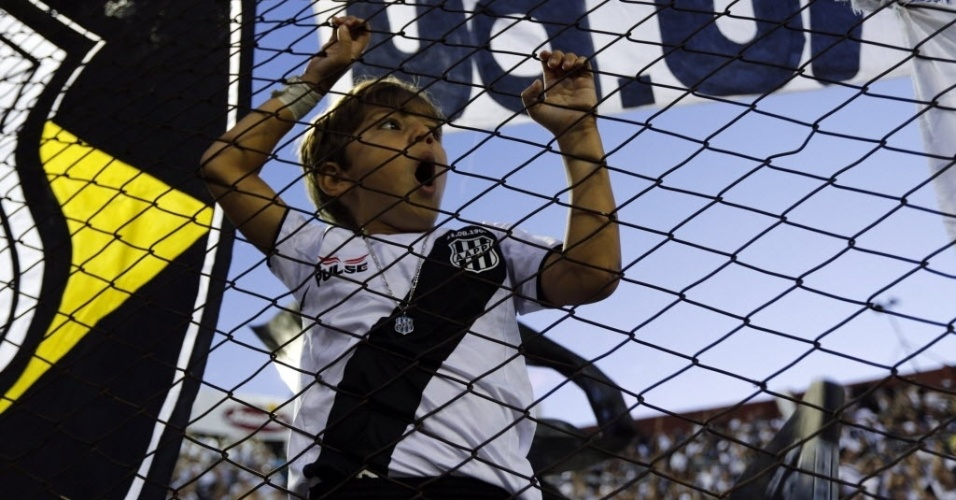 11.dez.2013 - Garotinho torcedor da Ponte Preta sobe nas grades da arquibancada para gritar pelo seu time na partida contra o Lanús