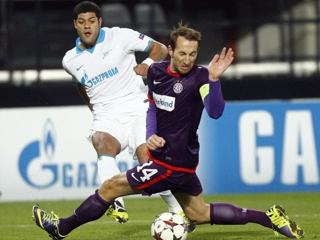 11.dez.2013 - Hulk, do Zenit, tenta chutar marcado por Ortlechner, do Austria Viena, durante jogo da Liga dos Campeões