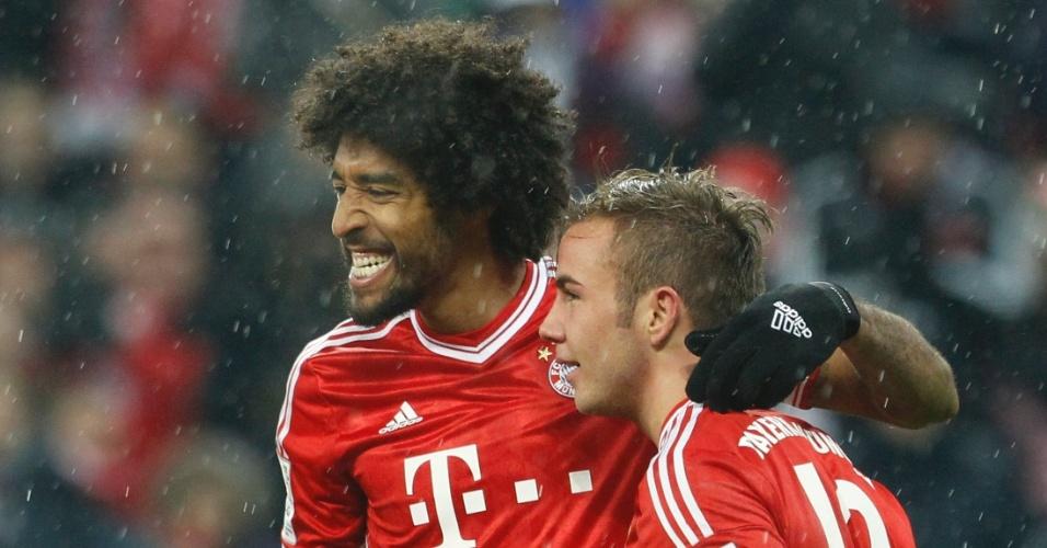 14.12.2013 - Brasileiro Dante (esquerda) mostra os dentes ao comemorar o gol de Gotze (direita) pelo Bayern