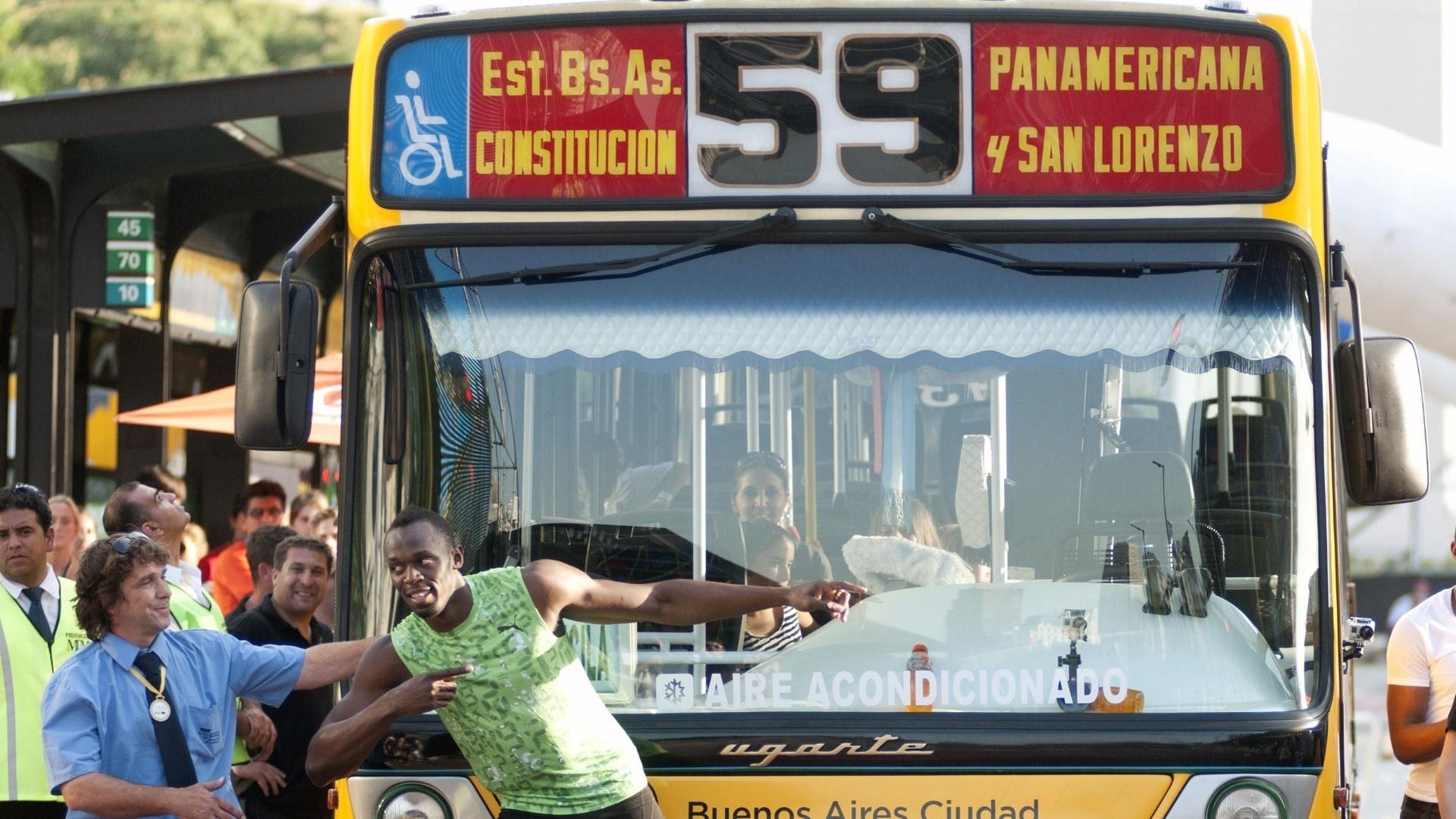 14.dez.2013 - Usain Bolt posa ao lado de ônibus após vencer desafio na Argentina