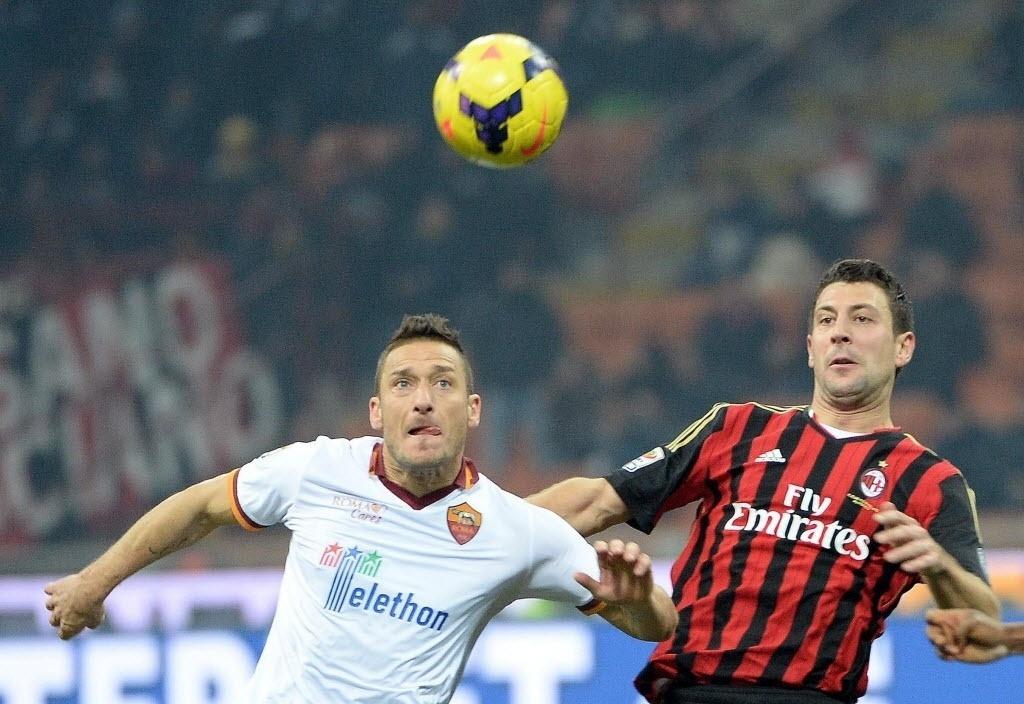 16.dez.2013 - Francesco Totti (esq.), ídolo da Roma que começou a partida no banco, se mostra recuperado de lesão e disputa a bola com Bonera, na partida do Campeonato Italiano contra o Milan