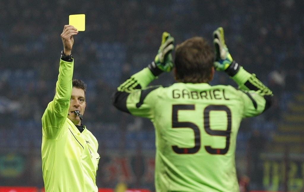 16.dez.2013 - Goleiro Gabriel recebe o cartão amarelo após cometer pênalti na partida entre Milan e Roma