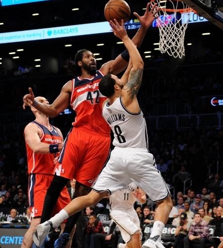 18.dez.2013 - Nenê tenta bloquear arremesso de Deron Williams, na vitória dos Wizards sobre os Nets por 113 a 107; Nenê saiu do banco e anotou 17 pontos
