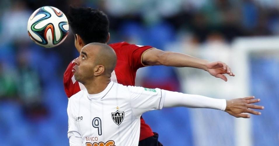 Tardelli disputa bola de cabeça com Conca no jogo entre Atlético-MG e Guangzhou (21.dez.2013)