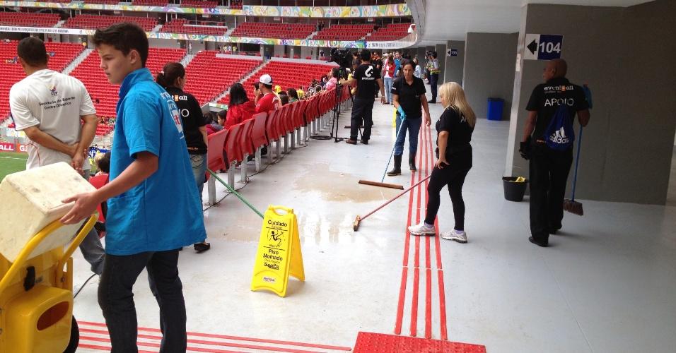 Funcionários da manutenção tentam conter com rodos água da chuva que vaza de emenda na cobertura do estádio Mané Garrincha, neste domindo (22), durante jogo de futebol feminino entre as seleções do Canadá e Escócia