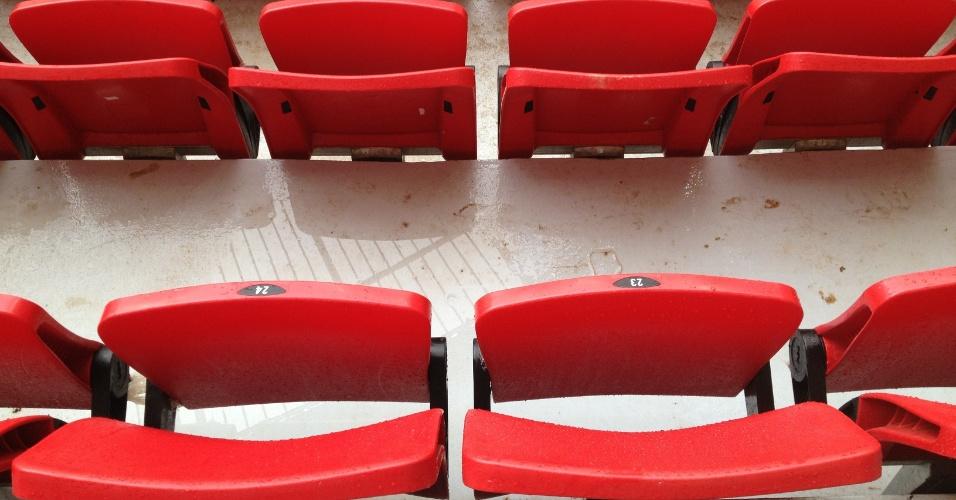 Imagem mostra cadeiras e piso molhados por conta de água da chuva que caiu por goteira em área coberta da arquibancada do estádio Mané Garrincha, em Brasília, neste domingo (22)
