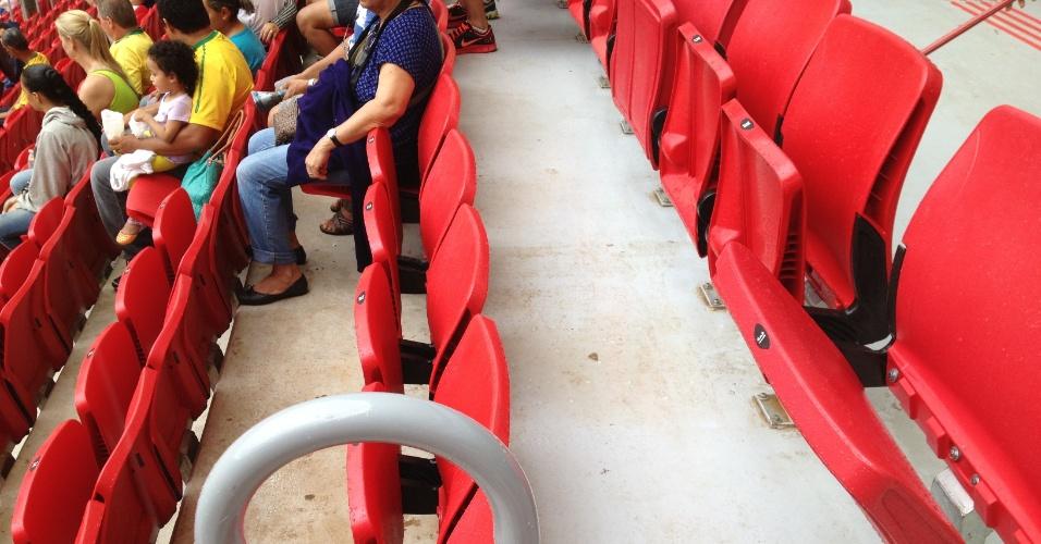 Imagem mostra detalhe de cadeiras e chão da arquibancada inferior molhados por água da chuva que vazou em goteiras pela cobertura do estádio Mané Garrincha, em Brasília: arena custou R$ 1,7 bilhão segundo TC-DFT