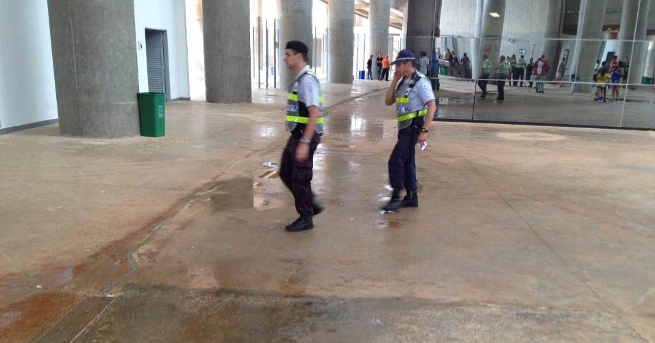 Policiais atravessam goteira em área interna coberta do estádio  Mané Garrincha, em Brasília, neste domingo: arena foi inaugurada em maio