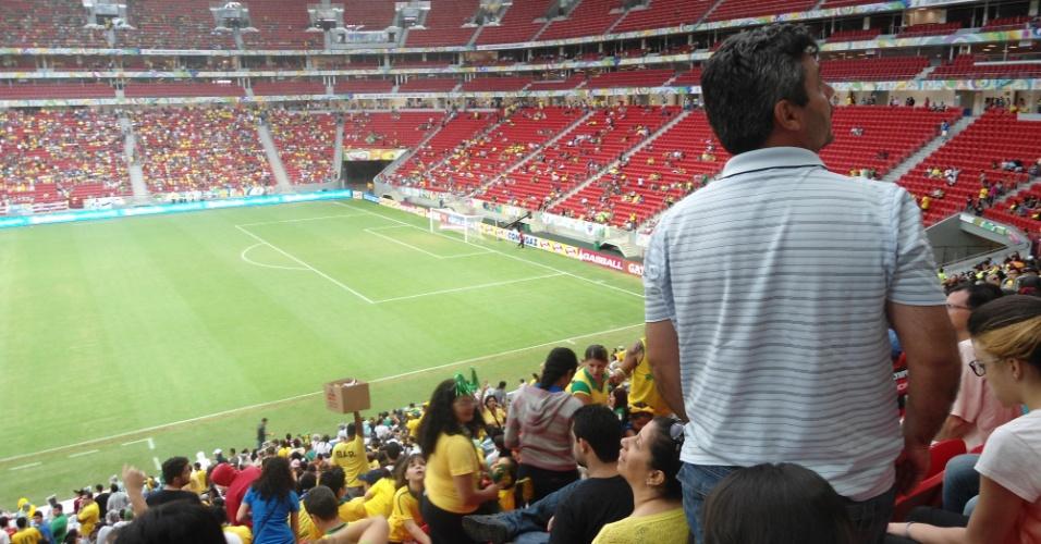 Torcedor foge de goteira em parte coberta da arquibancada no estádio Mané Garrincha, neste domingo (22): custo de R$ 1,7 bilhão