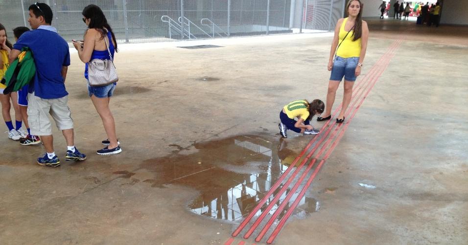 Torcedora atravessa com criança poça de água formada por goteira em área interna do estádio Mané Garrincha, em Brasília: vazamento por todos os lados