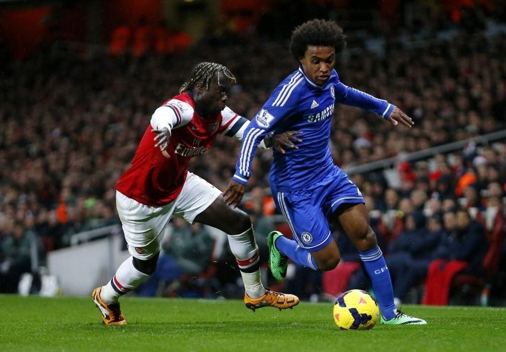 23.dez.2013 - Willian tenta escapar da marcação de Bacary Sagna, do Arsenal, durante jogo do Campeonato Inglês, em Londres