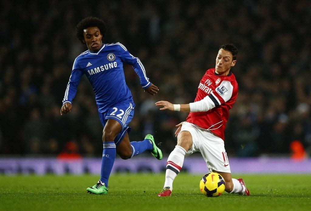 23.dez.2013 - Willian tenta tirar a bola de Özil durante jogo entre Arsenal e Chelsea pelo Campeonato Inglês