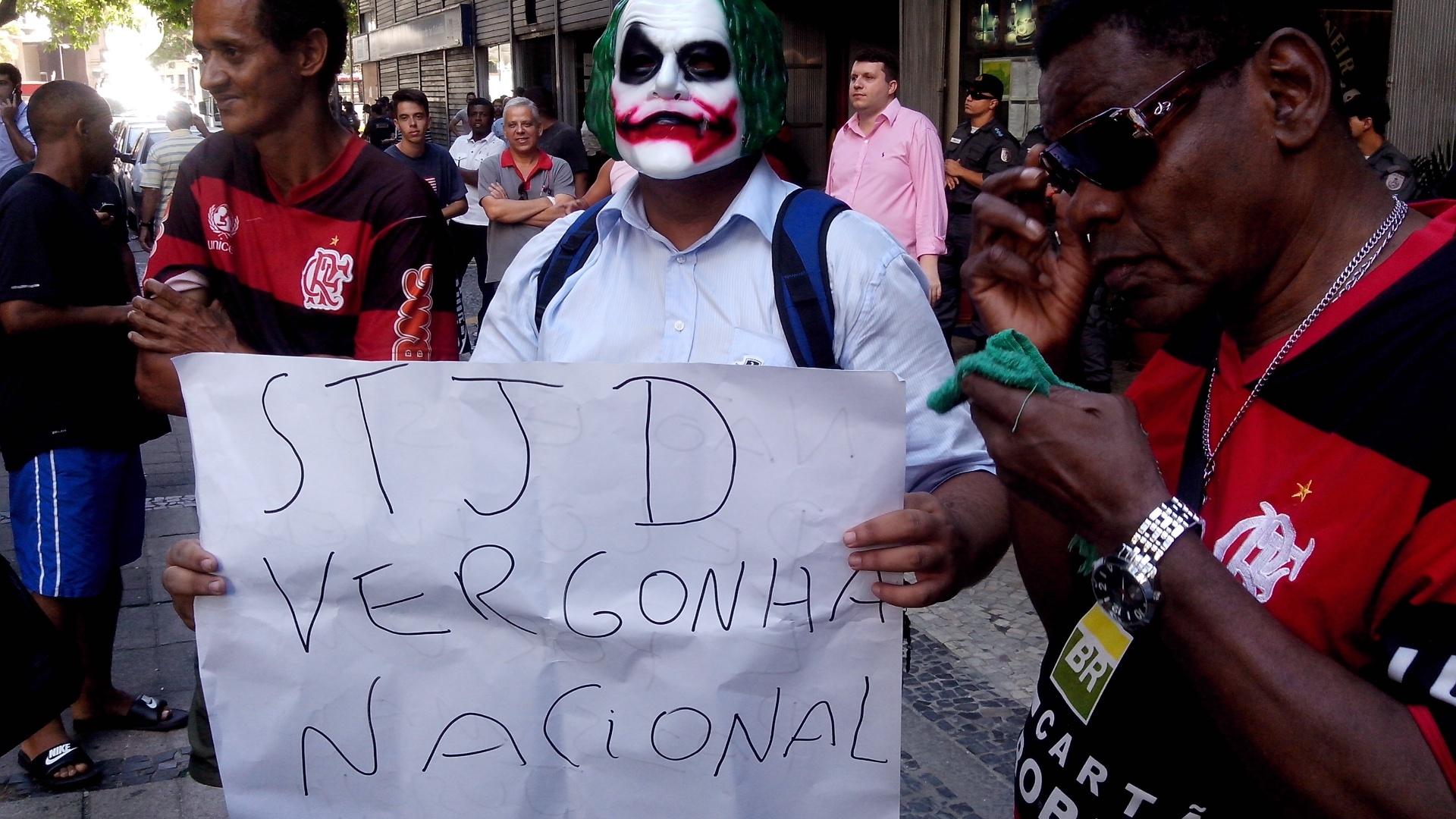27.dez.2013 - Torcedor com máscara do personagem Coringa leva cartaz que critica o STJD:
