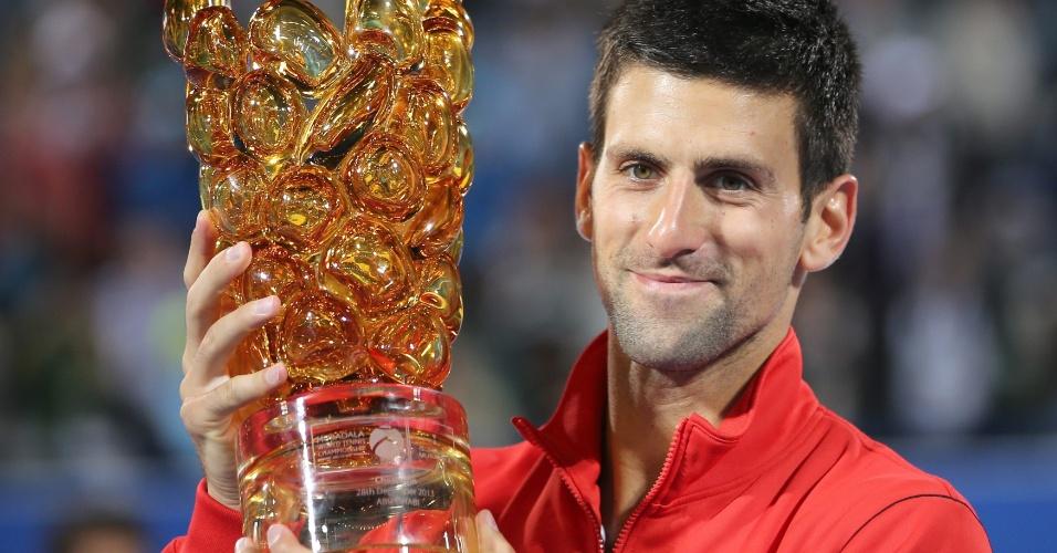 28.dez.2013 - Novak Djokovic mostra o troféu do Torneio de Abu Dhabi conquistado por ele após vitória na final sobre o espanhol David Ferrer