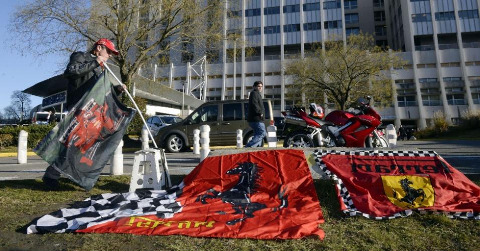 30.dez.2013 - Fã estende bandeiras da Ferrari em frente ao hospital de Grenoble, em apoio e homenagem a Schumacher