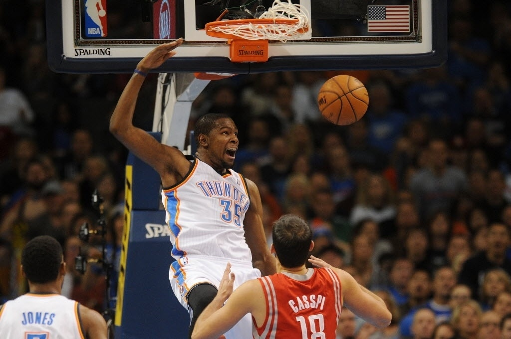 30.dez.2013 - Kevin Durant enterra a bola na cesta durante vitória do Oklahoma City Thunder sobre o Houston Rockets; o ala marcou 33 pontos e liderou o time na vitória por 117 a 86