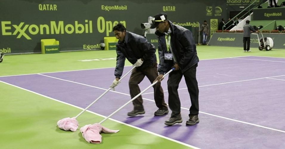 2. jan. 2014 - Equipe de manutenção usa panos para secar a quadra durante torneio de Doha