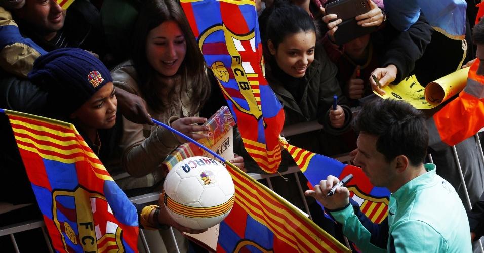 03.jan.2014 - Menina pede para Messi assinar bola do Barça