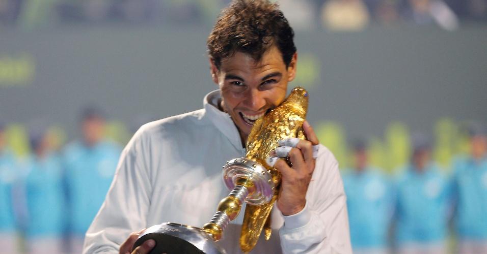 04.jan.2014 - Rafael Nadal morde o troféu após derrotar Gael Monfils na final do Torneio de Doha