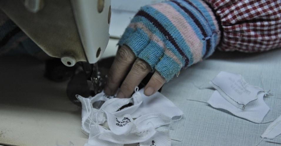 07.jan.2014 - Detalhe de uma trabalhadora chinesa costurando acessórios dos bonecos do mascote Fuleco