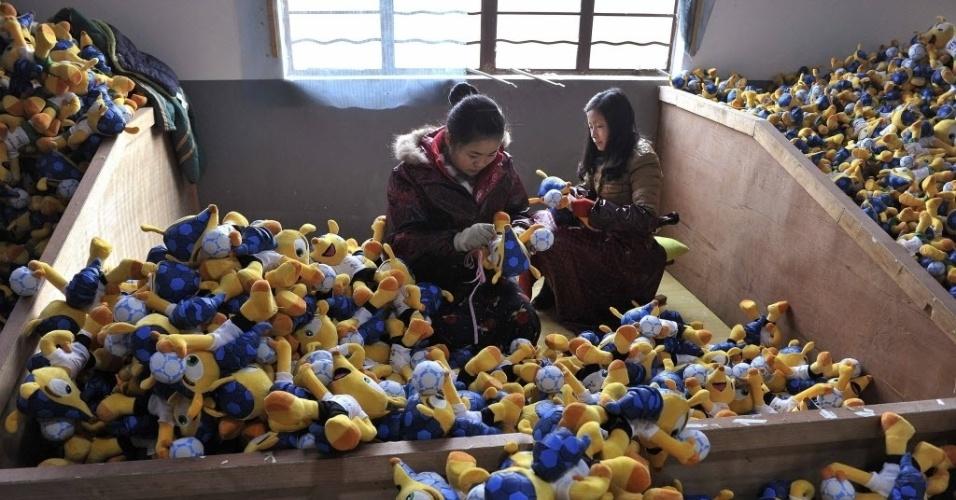 07.jan.2014 - Duas trabalhadoras costuram bonecos do Fuleco em fábrica na China