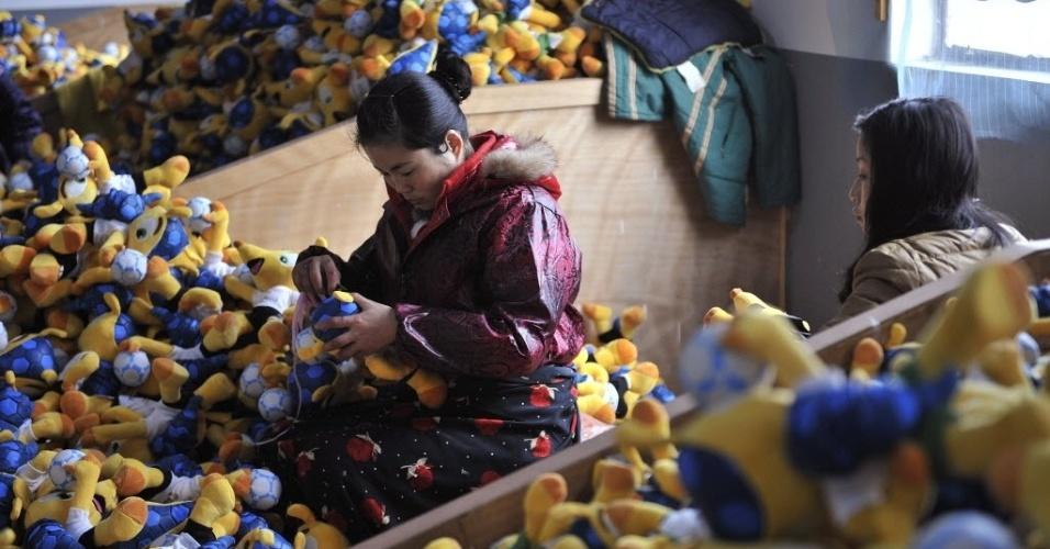 07.jan.2014 - Trabalhadora chinesa faz últimos ajustes em boneco do Fuleco, o mascote da Copa do Mundo do Brasil