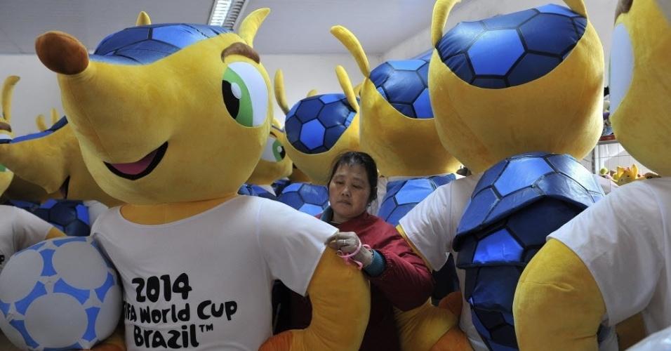 07.jan.2014 - Trabalhadora chinesa faz últimos ajustes em boneco gigante do Fuleco, o mascote da Copa do Mundo do Brasil