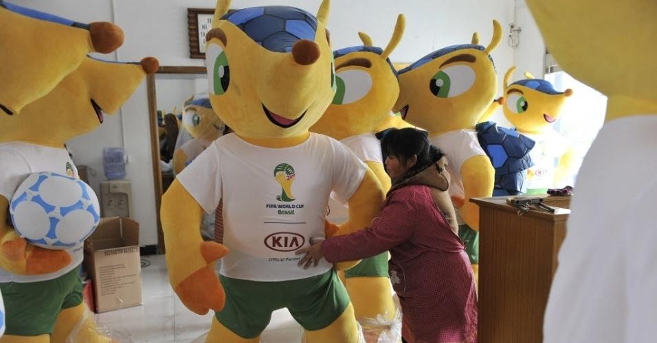 Trabalhadora chinesa faz últimos ajustes em boneco gigante do Fuleco, o mascote da Copa do Mundo do Brasil