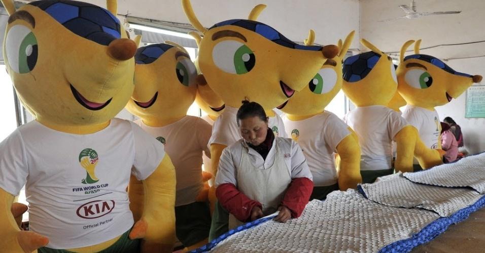 Trabalhadora desempenha as suas funções ao lado de alguns 'Fulecos gigantes' em fábrica chinesa