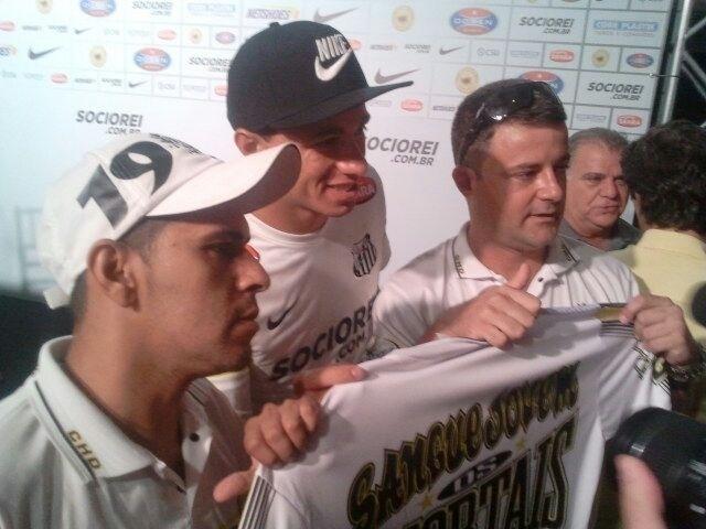 09.jan.2013 - Leandro Damião posa para foto ao lado de integrantes de torcida organizada do Santos na sua apresentação ao clube
