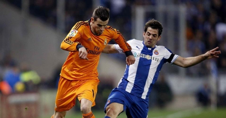 12. jan. 2014 - Jogador do Real Madrid, Gareth Bale tenta fugir da falta ao duelar com Victor Sanchez, do Espanyol, em partida do Campeonato Espanhol