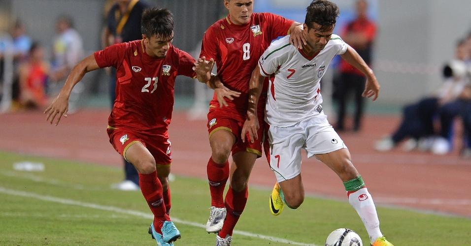 15.nov.2013 - Masoud Shohaei (d), do Irã, tenta se livrar dos marcadores durante a vitória por 3 a 0 sobre a Tailândia pelas eliminatórias da Copa da Ásia