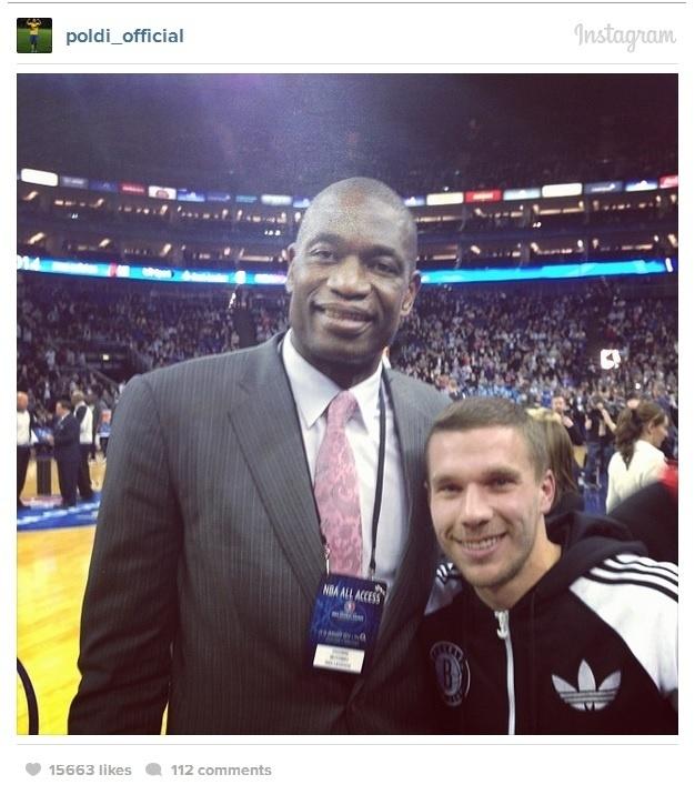 16.jan.2014 - Lukas Podolski tira foto com Mutombo em jogo da NBA disputado em Londres