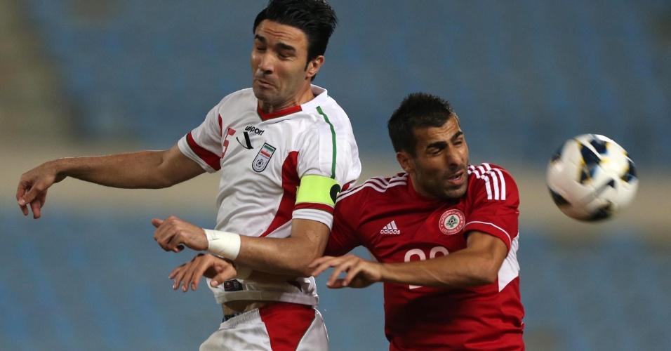 19.nov.2013 - Amir Hossein Sadeghi (e), do Irã, disputa jogada com Mohamad Ghaddar durante a vitória por 4 a 1 sobre o Líbano nas eliminatórias da Copa da Ásia