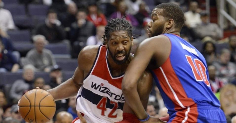 18.jan.2014 - Brasileiro Nenê, do Washington Wizards, tenta escapar da marcação de Greg Monroe, do Detroit Pistons durante jogo da NBA em Washington