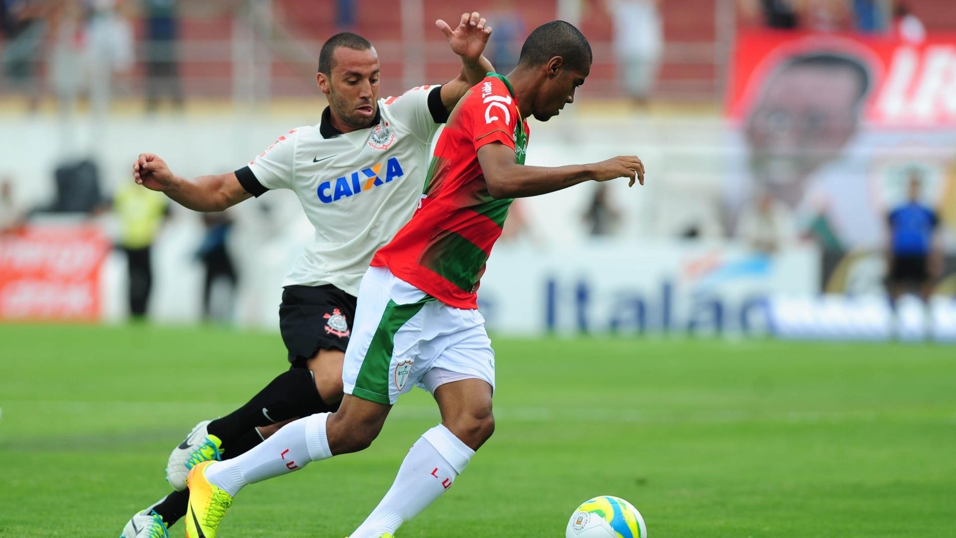 19.jan.2014 - Guilherme, do Corinthians, tenta roubar a bola de jogador da Portuguesa durante partida pelo Campeonato Paulista